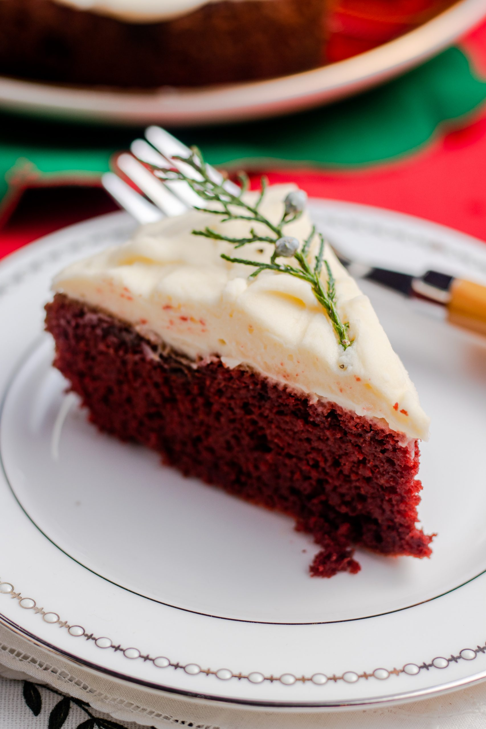 Slice of keto red velvet cake and cream cheese frosting adorned with fresh a juniper stem.