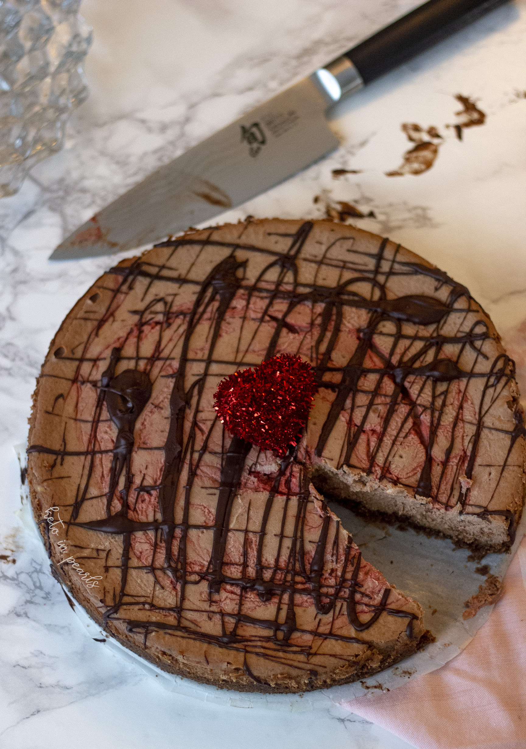 A keto cheesecake with decadent dark chocolate and bright notes of raspberry rests on a chocolate cookie crust. If you're a keto chocoholic, you will love this Dark Chocolate Raspberry Keto Cheesecake.
