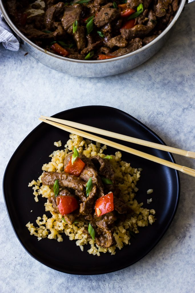 Low carb beef stir fry with peppers in an orange ginger sauce with cauliflower rice.