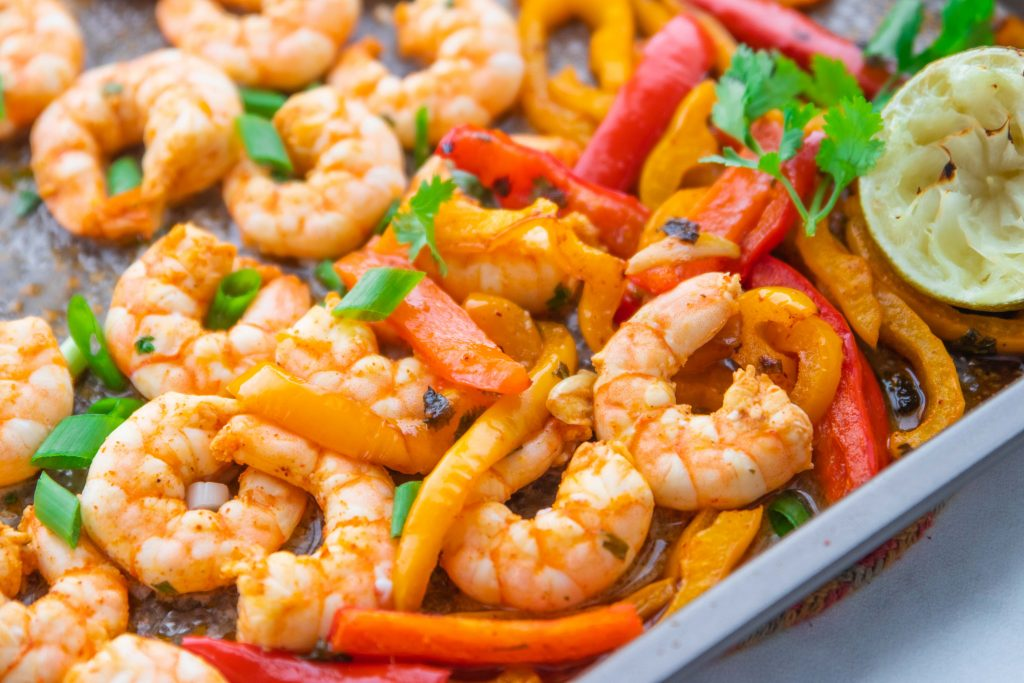 Jumbo shrimp cooked on a sheet pan with peppers in a chili lime marinade.