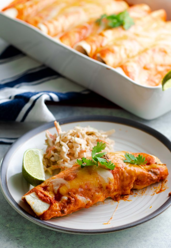 Low carb beef enchiladas with chipotle lime coleslaw and a lime wedge.