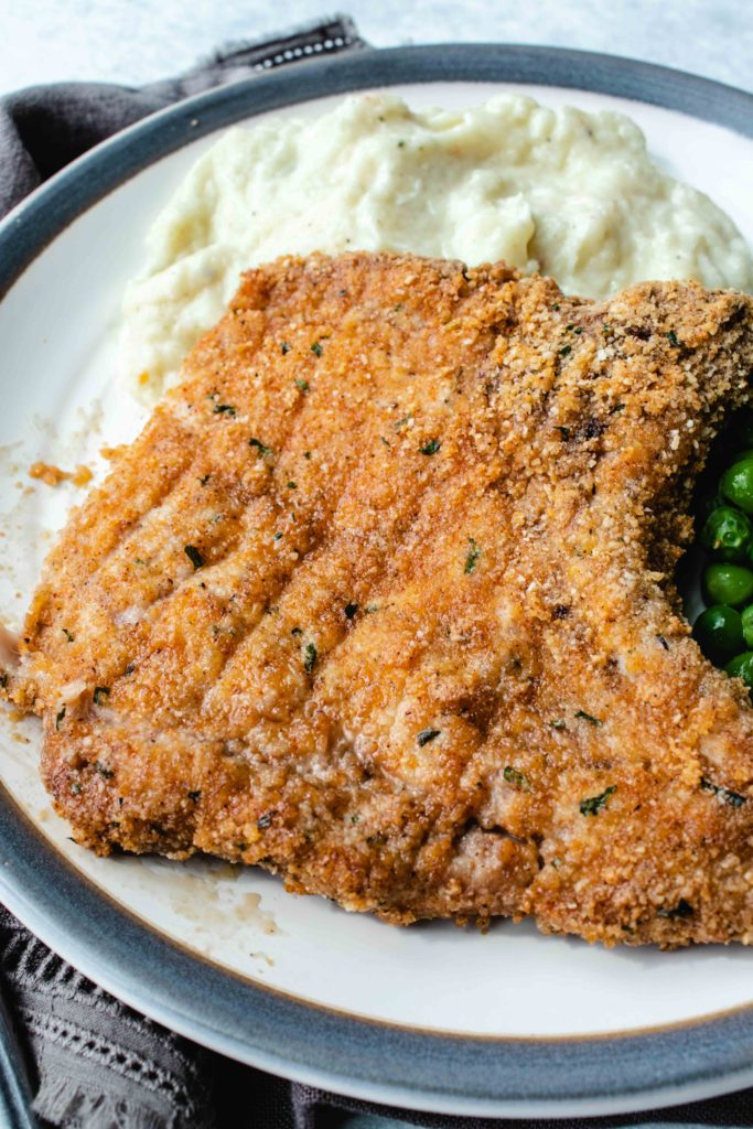 If you're in the market for a homestyle keto meal to feed your family, look no further. Keto pork chops are coated in a seasoned low carb breading and baked in an oven until crisp and tender. The ultimate family friendly keto supper!