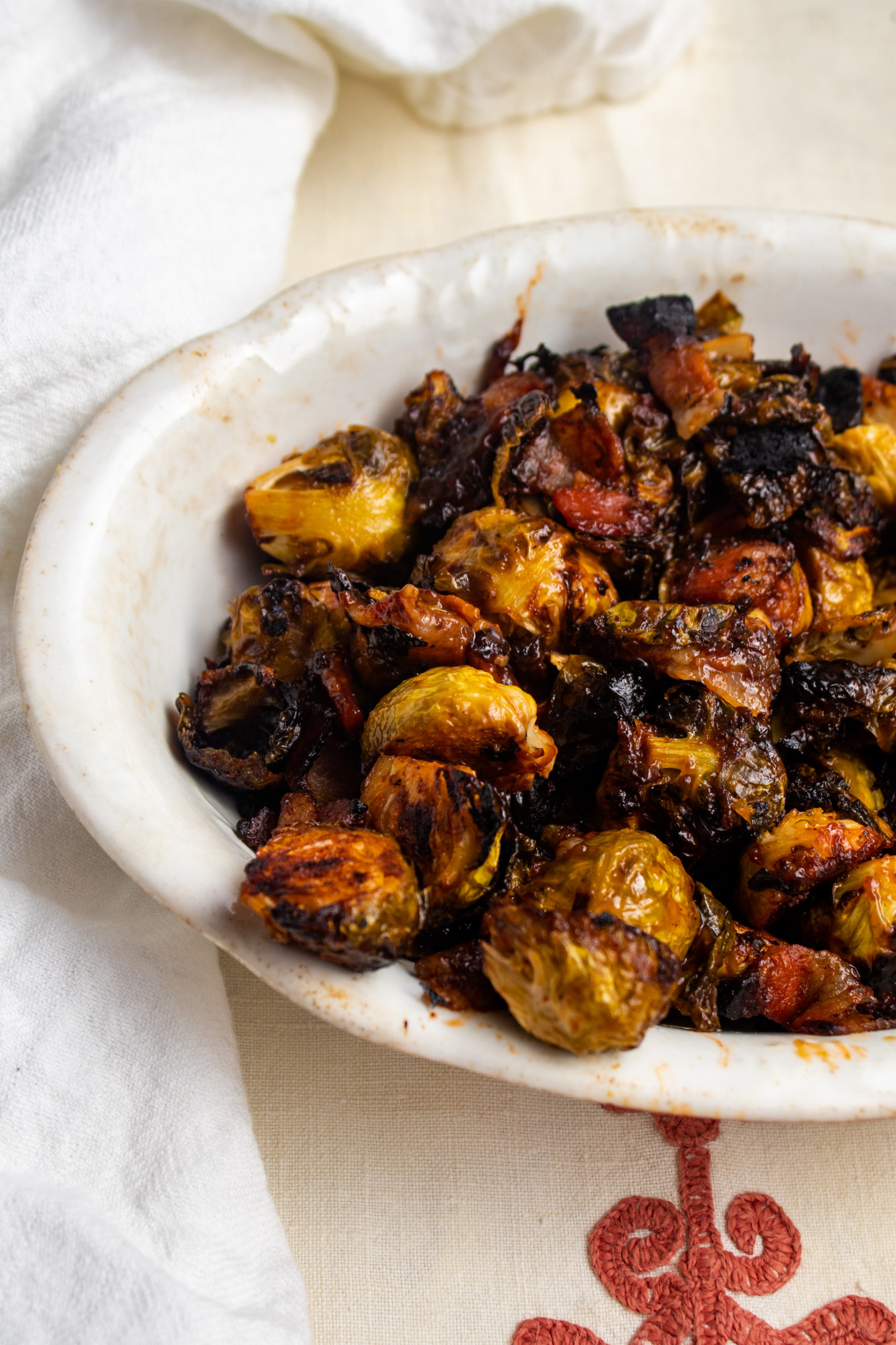 Brussel sprouts are roasted in the oven with bacon and a bbq glaze until crisp and caramelized. Learn how to make the best crispy bacon brussel sprouts.