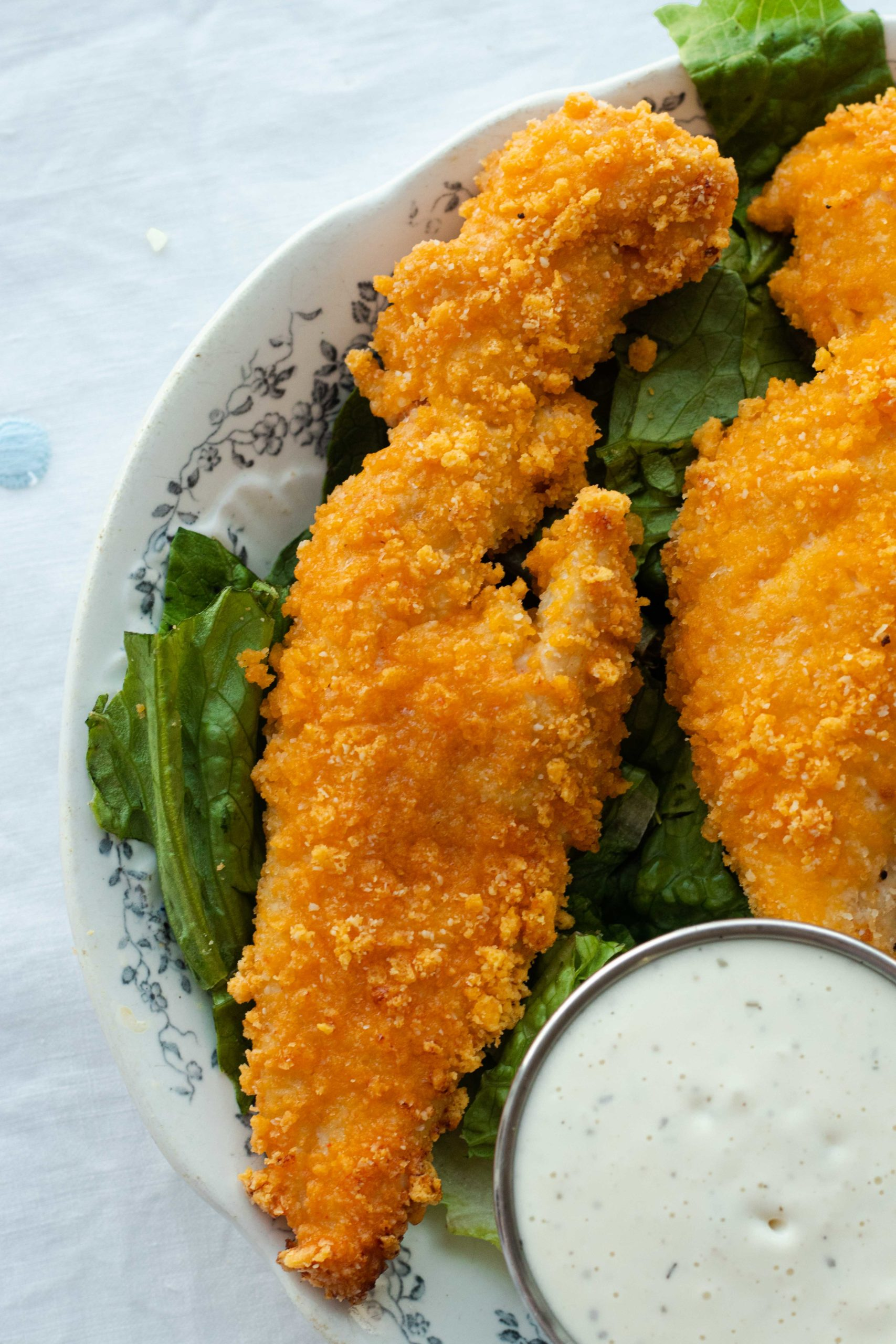 Chicken tenders are brined in buttermilk and then breaded in a crunchy cheese breading before getting baked to perfection. No eggs or pork rinds required!